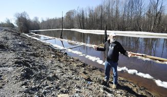 John Wathen, an environmentalist with the Waterkeeper Alliance, gestures at the site of a train derailment and oil spill near Aliceville, Ala., on Wednesday, May 5, 2014. Environmental regultors say cleanup and containment work is continuing at the site, but critics contend the accident and others show the danger of transporting large amounts of oil in tanker trains. (AP Photo/Jay Reeves)