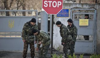 Ukrainian soldiers carry garbage outside the Ukrainian infantry base in Perevalne, Ukraine, Wednesday, March 12, 2014. The Group of 7 world leaders said in a statement released from the White House on Wednesday that they won't recognize results of a referendum for the Crimea region to split from Ukraine and join Russia.(AP Photo/Vadim Ghirda)