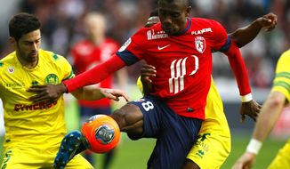 Lille's Salomon Kalou, center, controls the ball during his French League one soccer match against Nantes at the Lille Metropole stadium, in Villeneuve d'Ascq, northern France, Saturday, March. 15, 2014. (AP Photo/Michel Spingler)