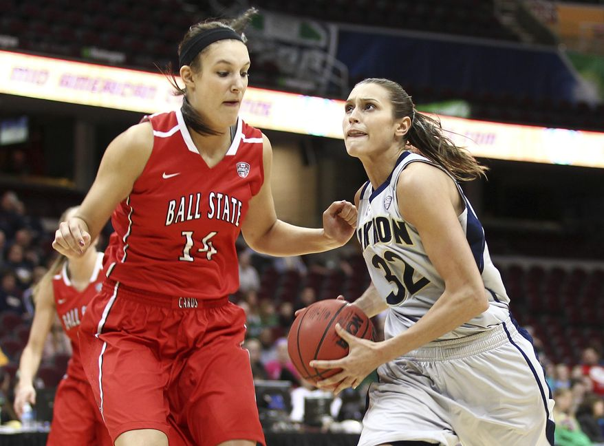 Akron's Rachel Tecca, right, eyes the basket as she drives against Ball State's Renee Bennett during the first half of an NCAA college basketball game in the championship of the Mid-American Conference tournament Saturday, March 15, 2014, in Cleveland. (AP Photo/Aaron Josefczyk)