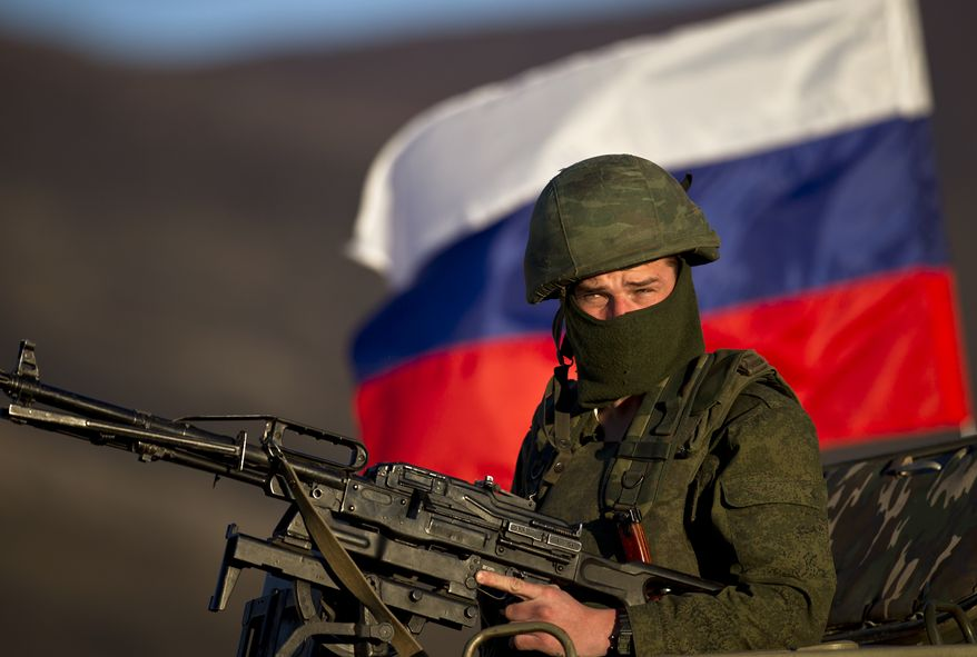 A pro-Russian soldier is back dropped by Russia flag while manning a machine-gun outside an Ukrainian military base in Perevalne, Ukraine, Saturday, March 15, 2014. Tensions are high in the Black Sea peninsula of Crimea, where a referendum is to be held Sunday on whether to split off from Ukraine and seek annexation by Russia. (AP Photo/Vadim Ghirda)
