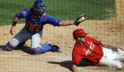 New York Mets catcher Anthony Recker, left, tags out St. Louis Cardinals' Stephen Piscotty as he slides into home plate off a fly ball by teammate Scott Moore in the eighth inning of an exhibition spring training baseball game, Sunday, March 16, 2014, in Jupiter, Fla. (AP Photo/David Goldman)