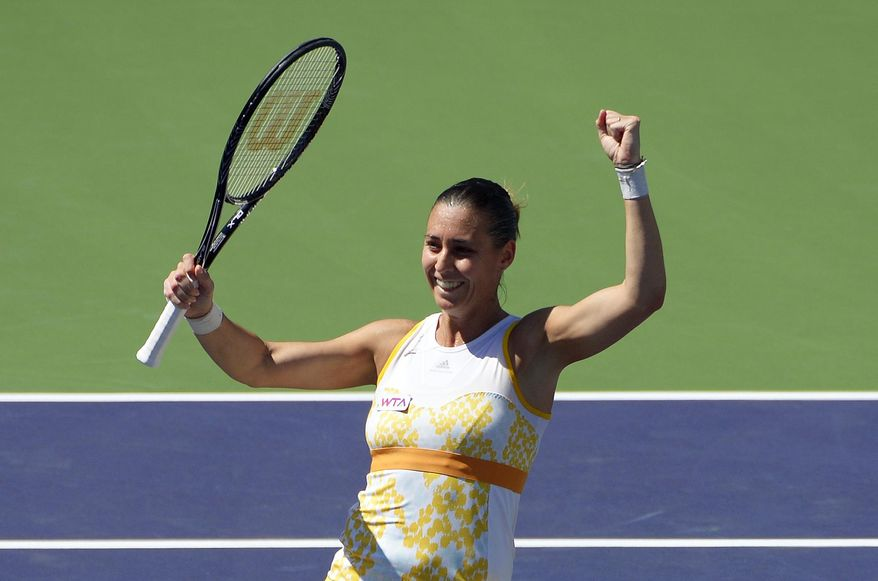 Flavia Pennetta, of Italy, raises her racquet after she beat Agnieszka Radwanska, of Poland, 6-2, 6-1, in the final round of the BNP Paribas Open tennis tournament, Sunday, March 16, 2014, in Indian Wells, Calif. (AP Photo/Mark J. Terrill)