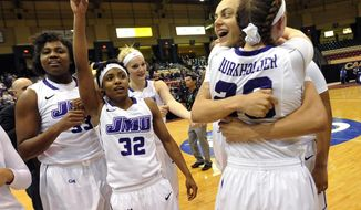 James Madison's Jazmon Gwathmey, second from right, hugs Kirby Burkholde after defeating Delaware 70-45 in the NCAA college basketball game for the Colonial Athletic Association tournament championship Sunday, March 16, 2014, in Upper Marlboro, Md. Also pictured, at left, is Angela Mickens (32) and Lauren Okafor (33).(AP Photo/Gail Burton)