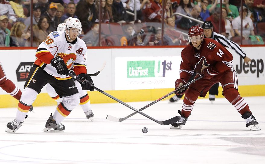 Calgary Flames' Curtis Glencross, left, and Phoenix Coyotes' Jeff Halpern chase down the puck during the first period of an NHL hockey game on Saturday, March 15, 2014, in Glendale, Ariz. (AP Photo/Matt York)