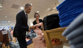 President Obama, assisted by Gap employee Susan Panariello, uses a shopping trip to make his case for raising the national minimum wage. (Associated Press)