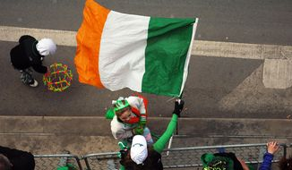 A parade reveler proudly waves the flag of Ireland on Saturday, March 15, 2014, during the 53rd Scranton St.Patrick's Day Parade held in downtown Scranton, Pennsylvania.  (AP Photo / The Scranton Times-Tribune, Butch Comegys)  MANDATORY CREDIT