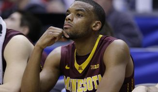 Minnesota guard Andre Hollins watches from the bench in the second half of an NCAA college basketball game against Wisconsin in the quarterfinals of the Big Ten Conference tournament Friday, March 14, 2014, in Indianapolis. Wisconsin won 83-57. (AP Photo/Michael Conroy)