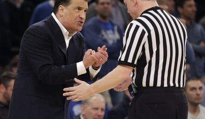 St. John's head coach Steve Lavin, left, argues with a referee during the second half of an NCAA college basketball game against Providence in the quarterfinals of the Big East Conference tournament at Madison Square Garden, Thursday, March 13, 2014 in New York. Providence defeated St. John's 79-74.(AP Photo/Seth Wenig)