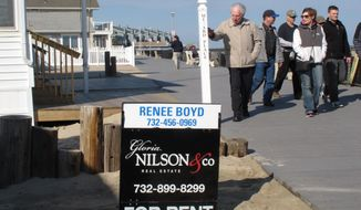 This March 8, 2014 photo shows strollers on the boardwalk in Point Pleasant Beach N.J. walking past a home being offered as a summer rental. The rental market at the Jersey shore is developing later than usual this year in parts of the region, due to a highway reconstruction project, uncertainty about which beaches will be open this summer, and a seemingly unending string of winter storms that have kept people from driving to the shore to check out vacation spots. The shore towns are counting on this summer to be better than last year's as they struggle to recover from the Oct. 2012 storm. (AP Photo/Wayne Parry)