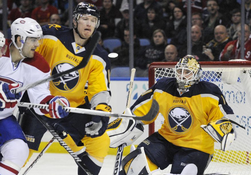 Montreal Canadiens left winger Max Pacioretty, left, battles for the puck with Buffalo Sabres defenseman Christian Ehrhoff, center, of Germany, while Sabres goaltender Jhonas Enroth, right, of Sweden, watches the incoming shot during the second period of an NHL hockey game in Buffalo, N.Y., Sunday March 16, 2014. (AP Photo/Gary Wiepert)