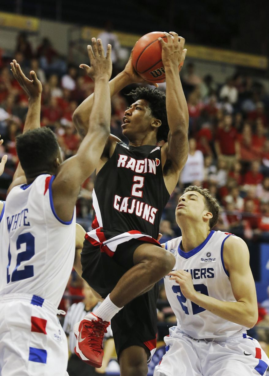 Louisiana Lafayette guard Elfrid Payton (2) shoots over Georgia State guards Devonta White (12) and J. R. Hunter (22) as in the first half of an NCAA college basketball game for the Sun Belt Conference tournament championship in New Orleans, Sunday, March 16, 2014. (AP Photo/Bill Haber)
