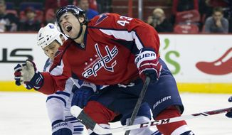 Toronto Maple Leafs defenseman Tim Gleason, left, defends against Washington Capitals right wing Tom Wilson during the second period of an NHL hockey game on Sunday, March 16, 2014, in Washington. (AP Photo/ Evan Vucci)