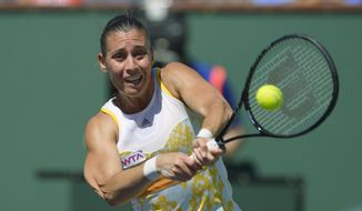 Flavia Pennetta, of Italy, hits to Agnieszka Radwanska, of Poland, in their final round at the BNP Paribas Open tennis tournament, Sunday, March 16, 2014, in Indian Wells, Calif. (AP Photo/Mark J. Terrill)