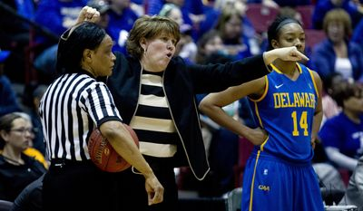 Delaware head coach Tina Martin, center, talks to her players in the second half of an NCAA college basketball game against James Madison for the Colonial Athletic Association tournament championship in Upper Marlboro, Md., on Sunday, March 16, 2014. (AP Photo/Jose Luis Magana)