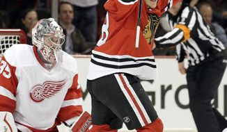 Chicago Blackhawks' Ben Smith (28), right, celebrates after Nick Leddy (8) scored a goal as Detroit Red Wings goalie Jimmy Howard (35) reacts during the second period of an NHL hockey game in Chicago, Sunday, March 16, 2014. (AP Photo/Nam Y. Huh)