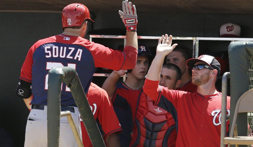 Washington Nationals' Steven Souza, left, is congratulated in the dugout after his second home run of the game during the fourth inning of a spring exhibition baseball game against the Houston Astros in Kissimmee, Fla., Sunday, March 16, 2014. (AP Photo/Carlos Osorio)