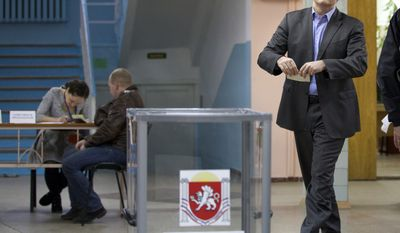 The head of Crimea's unrecognised Russian-backed government Sergei Aksyonov goes to cast his ballot at a polling station in Simferopol, Ukraine, Sunday, March 16, 2014. Residents of Ukraine's Crimea region are voting in a contentious referendum on whether to split off and seek annexation by Russia. (AP Photo/Ivan Sekretarev)