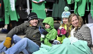 From left, J.T. Delcamp sits with his kids, Dominic, 6, and Addalynn, 9, and with Kellie Bauss, as they watch the annual St. Patrick's day parade in Detroit, Michigan on March 16, 2014. Detroit's parade began at noon and featured pipe and drum bands, color guard units, floats and clowns. (AP Photo/Detroit News, Robin Buckson)  DETROIT FREE PRESS OUT; HUFFINGTON POST OUT; MANDATORY CREDIT