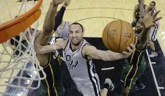 San Antonio Spurs' Manu Ginobili (20), of Argentina, shoots around Utah Jazz's Derrick Favors (15) during the first half of an NBA basketball game, Sunday, March 16, 2014, in San Antonio. (AP Photo/Eric Gay)