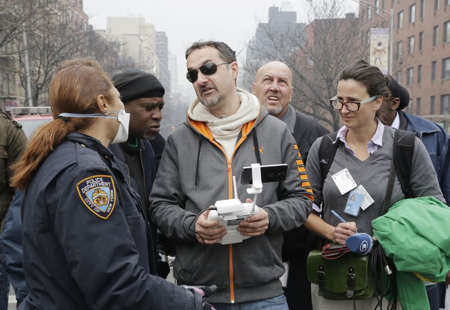 FILE - This March 12, 2104 file photo shows a New York City police officer, left, telling Brian Wilson, center, to land the drone that he was flying over the scene of an explosion that leveled two apartment buildings in East Harlem in New York. Wilson says he uses the aerial drone to document buildings, weddings and news events. The Federal Aviation Administration bars commercial use of drones no matter how seemingly benign. Officials say rules to address the special safety challenges associated with unmanned aircraft need to be in place before they can share the sky with manned aircraft and final regulations could be years away. But tempting technology and an eager marketplace are outrunning the aviation agency's best intentions. Photographers, real estate agents, moviemakers, and others are hurrying to embrace the technology. (AP Photo/Mark Lennihan, File)