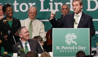 Prime Minister Enda Kenny of Ireland, right, holds a badge while speaking at the annual St. Patrick's Day Breakfast in Boston, as host state Sen. Linda Dorcena Forry, left, looks on, March 16, 2014.  (AP Photo/Michael Dwyer)
