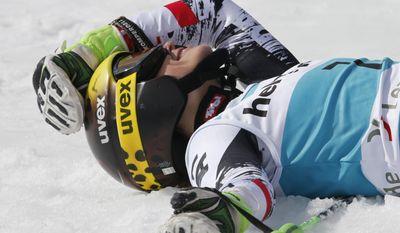 Austria's Anna Fenninger lies on the snow after winning an alpine ski World Cup giant slalom race and overall World Cup champion, in Lenzerheide, Switzerland, Sunday, March 16, 2014. (AP Photo/Armando Trovati)