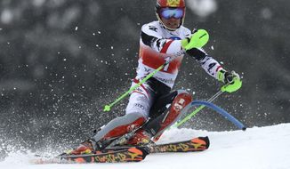 Marcel Hirscher of Austria clears a gate during the first run of the men's slalom race at the alpine skiing World Cup finals in Lenzerheide, Switzerland, Sunday, March 16, 2014. (AP Photo/Keystone, Jean-Christophe Bott)