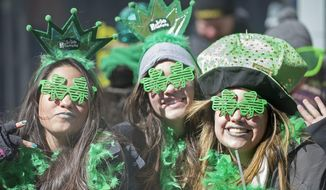 Spectators smile as the watch the annual St. Patrick's Day parade in Montreal, Sunday, March 16, 2014. (AP Photo/The Canadian Press, Graham Hughes)