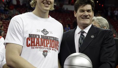 Mountain West Conference commissioner Craig Thompson, right, presents New Mexico's Cameron Bairstow with a trophy for the tournament's most valuable player after an NCAA college basketball game against New Mexico, Saturday, March 15, 2014, in Las Vegas. (AP Photo/Isaac Brekken)