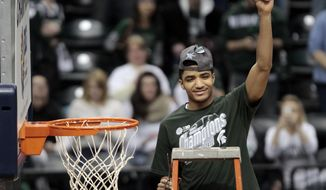 Michigan State guard Gary Harris holds up a piece of the net after his team defeated Michigan 69-55 in an NCAA college basketball game in the championship of the Big Ten Conference tournament on Sunday, March 16, 2014, in Indianapolis. (AP Photo/AJ Mast)