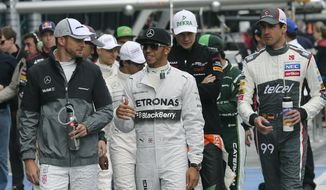 McLaren driver Jenson Button of Britain, left, and Mercedes driver Lewis Hamilton also of Britain chat as they walk along the pit lane during the Australian Formula One Grand Prix at Albert Park in Melbourne, Australia, Sunday, March 16, 2014. (AP Photo/Rob Griffith)