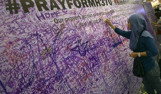 A woman leaves a message for passengers aboard a missing Malaysia Airlines plane, at a shopping mall in Petaling Jaya, near Kuala Lumpur, Malaysia, Sunday, March 16, 2014. Malaysian authorities Sunday were investigating the pilots of the missing jetliner after it was established that whoever flew off with the Boeing 777 had intimate knowledge of the cockpit and knew how to avoid detection when navigating around Asia. (AP Photo/Lai Seng Sin)