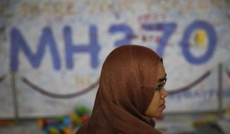 A Malaysian women stand in front of messages board and well wishes to people involved with the missing Malaysia Airlines jetliner MH370, Sunday, March 16, 2014 in Sepang, Malaysia. The Malaysian passenger jet missing for more than a week had its communications deliberately disabled and its last signal came about seven and a half hours after takeoff, meaning it could have ended up as far as Kazakhstan or deep in the southern Indian Ocean, Malaysia's Prime Minister Najib Razak said Saturday. (AP Photo/Vincent Thian)