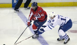 Washington Capitals right wing Joel Ward (42) fights against Toronto Maple Leafs defenseman Paul Ranger (15) for control of the puck during the third period of an NHL hockey game on Sunday, March 16, 2014, in Washington. The Capitals won 4-2. (AP Photo/Evan Vucci)