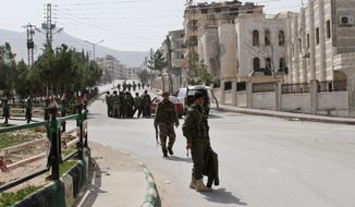 Syrian government forces walk after being deployed in Yabroud town, Syria, Sunday, March 16, 2014. Syrian troops backed by Hezbollah fighters seized a key rebel supply town on the Lebanese border on Sunday, driving them from the area and scoring a major blow against them in the three-year-old-conflict. The fall of Yabroud immediately emboldened government forces to attack nearby rebel-held towns, pressing forward in what has been nearly a yearlong advance against rebels fighting to overthrow President Bashar Assad. (AP Photo)