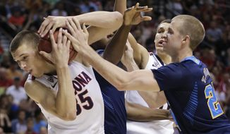 Arizona's Kaleb Tarczewski battles for a rebound against UCLA's Travis Wear in the second half during the championship game of the NCAA Pac-12 conference college basketball tournament, Saturday, March 15, 2014, in Las Vegas. UCLA won 75-71. (AP Photo/Julie Jacobson)