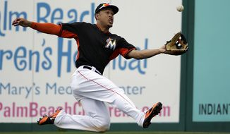 Miami Marlins' Giancarlo Stanton makes a catch for an out on a fly ball hit by New York Mets' Eric Campbell in the fourth inning of an exhibition spring training baseball game, Monday, March 17, 2014, in Jupiter, Fla. (AP Photo/David Goldman)