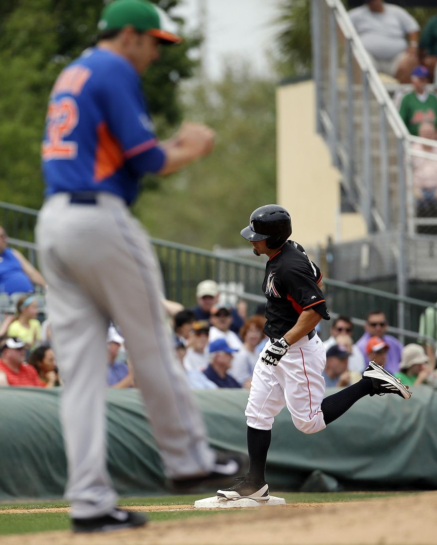 Miami Marlins' Reed Johnson, right, rounds third base past New York Mets starting pitcher John Lannan after hitting a home run in the fourth inning of an exhibition spring training baseball game, Monday, March 17, 2014, in Jupiter, Fla. (AP Photo/David Goldman)
