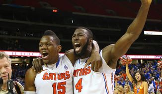 Florida forward Will Yeguete, left, and center Patric Young celebrate after beating Kentucky in an NCAA college basketball game in the championship for the Southeastern Conference tournament, Sunday, March 16, 2014, in Atlanta. Florida won 61-60. (AP Photo/Atlanta Journal-Constitution, Curtis Compton)