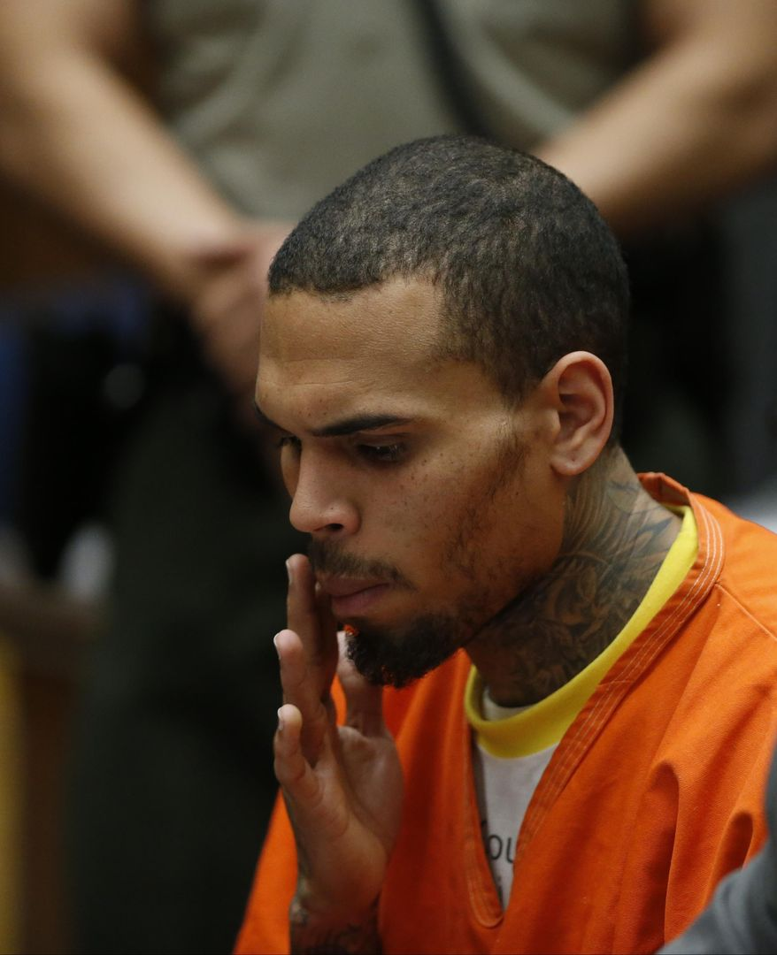 R&B singer Chris Brown appears in Los Angeles Superior Court with his attorney Mark Geragos, on Monday, March 17, 2014. Brown will spend another month in jail after a judge said Monday he was told the singer made troubling comments in rehab about being good at using guns and knives. The singer was arrested on Friday, March 14, 2014, after he was dismissed from a Malibu facility where he was receiving treatment for anger management, substance abuse and issues related to bipolar disorder. (AP Photo/Lucy Nicholson, Pool)