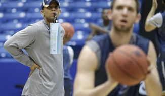 Mount St. Mary's head coach Jamion Christian watches his players shoot free throws during practice for an NCAA college basketball tournament game, Monday, March 17, 2014, in Dayton, Ohio. Albany plays Mount St. Mary's on Tuesday in a first round game. (AP Photo/Al Behrman)