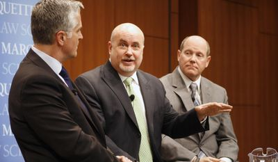 Rep. Mark Pocan, center, speaks while Rep. Reid Ribble, right, and panel moderator Mike Gousha, left, listen Monday, March 17, 2014, at Marquette University Law School in Milwaukee. Ribble, a Republican from the Fox Valley, and Pocan, a Madison Democrat, belong to No Labels Problem Solvers, a bipartisan group of lawmakers who meet weekly to get to know each other and discuss issues. (AP Photo/M.L. Johnson)