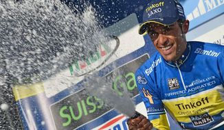 Overall leader Alberto Contador sprays sparkling wine as he celebrates on the podium after completing the sixth stage of the Tirreno Adriatico cycling race, from Bucchianico to Porto Sant'Elpidio, Italy, Monday, March 17, 2014. Mark Cavendish took advantage of a crash to easily win the sixth and penultimate stage of the Tirreno-Adriatico race Monday, and Alberto Contador maintained his overall lead. When several riders went down with little more than a kilometer to go, the pack split and Cavendish's Omega Pharma-Quick Step train was virtually alone in front. (AP Photo/Gian Mattia D'Alberto, Lapresse)