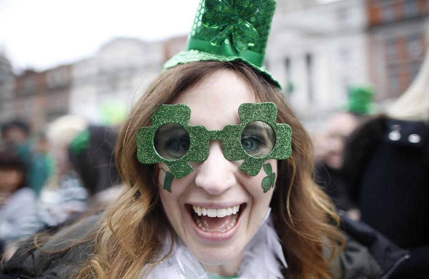 A woman enjoys the party atmosphere during the St Patrick's day parade in Dublin, Ireland, Monday March, 17, 2014.  The world's largest parade celebrating Irish heritage set off on a cold and gray morning, the culmination of a weekend of St. Patrick's Day revelry. (AP Photo/Peter Morrison)