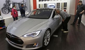 Tesla representative John Van Cleave, right, shows customers Sarah and Robert Reynolds, left, and Vince Giardina, a new Tesla all electric car, Monday, March 17, 2014, at a Tesla showroom inside the Kenwood Towne Centre in Cincinnati. Ohio auto dealers are sparring at the Statehouse with the California-based Tesla, which is selling it's next generation electric cars from three Ohio storefronts. Lawmakers in Ohio and other states are trying to block Tesla direct sales on grounds they undercut traditional auto dealerships. (AP Photo/Al Behrman)