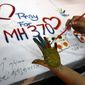 Associated Press   A woman paints her palm with water colors during an event for passengers aboard a missing Malaysia Airlines plane, in Kuala Lumpur, Malaysia, Monday, March 17, 2014. Authorities now believe someone on board the Boeing 777 shut down part of the aircraft's messaging system about the same time the plane with 239 people on board disappeared from civilian radar. But an Inmarsat satellite was able to automatically connect with a portion of the messaging system that remained in operation, similar to a phone call that just rings because no one is on the other end to pick it up and provide information. No location information was exchanged, but the satellite continued to identify the plane once an hour for four to five hours after it disappeared from radar screens.