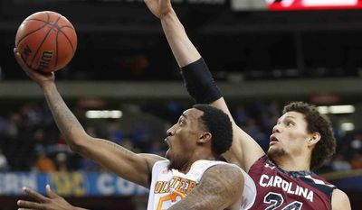 Tennessee guard Jordan McRae (52) shoots against South Carolina forward Michael Carrera (24) during the second half of an NCAA college basketball game in the quarterfinal round of the Southeastern Conference men's tournament, Friday, March 14, 2014, in Atlanta. (AP Photo/John Bazemore)