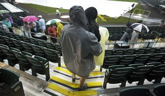Baseball fans leave the spring exhibition baseball game between the Pittsburgh Pirates and the New York Yankees after being called due to rain in Bradenton, Fla., Monday, March 17, 2014. (AP Photo/Carlos Osorio)