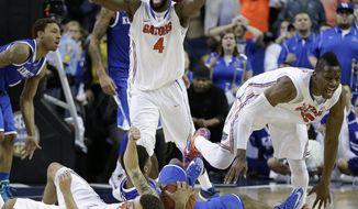 Florida center Patric Young (4) celebrates with Florida forward Will Yeguete (15) after the second half of an NCAA college basketball game against Kentucky in the Championship round of the Southeastern Conference men's tournament, Sunday, March 16, 2014, in Atlanta. Florida won 61-60. (AP Photo/Steve Helber)